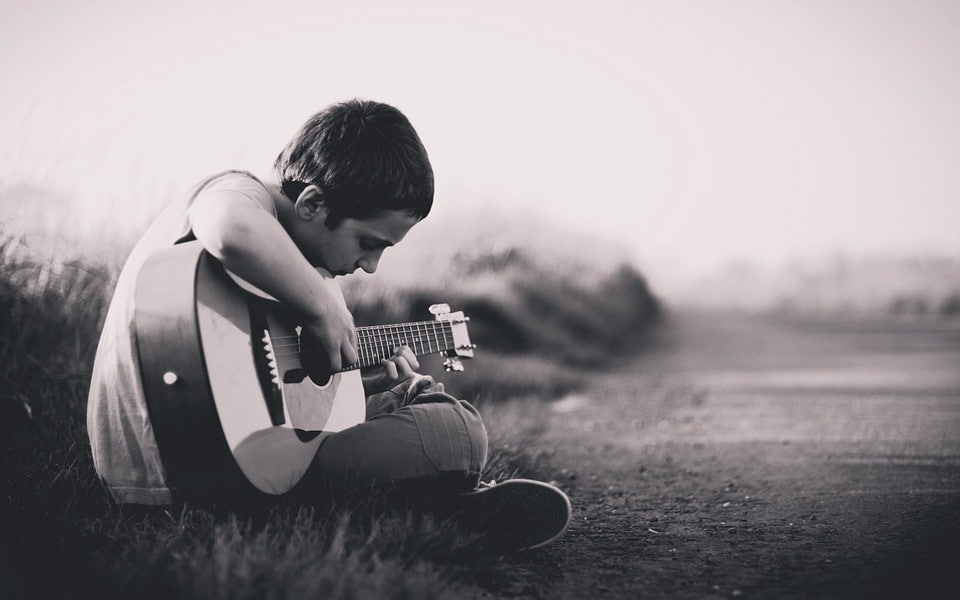 boy playing guitar alone on the road
