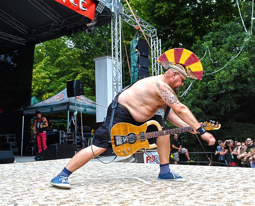 man playing his guitar in a festival as stress reliever