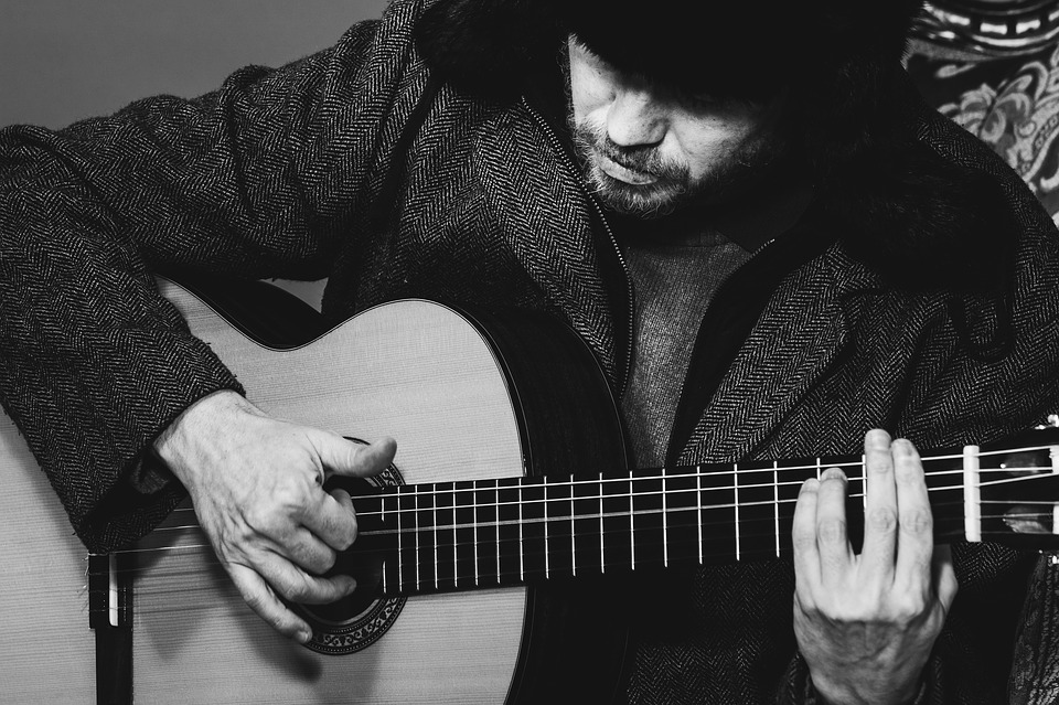 man playing music using his guitar to improve memory