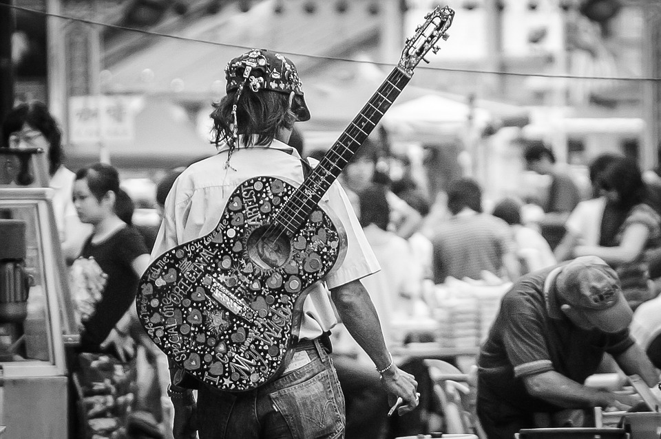 man carrying his guitar on his back for a walk