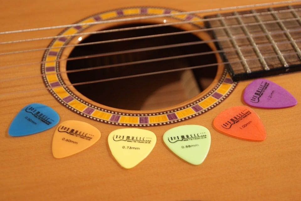 different colors of flat picks on the guitar