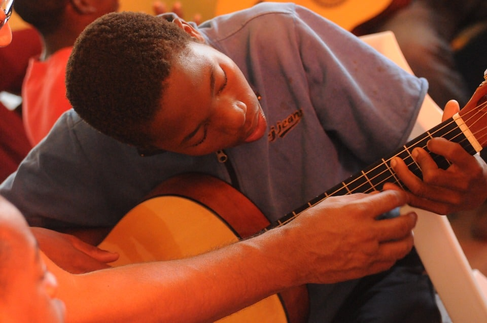 a student is eagerly learning how to play a guitar