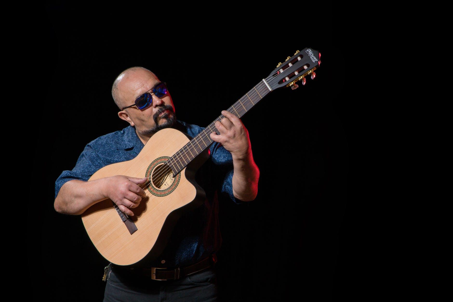 man playing the guitar using picking