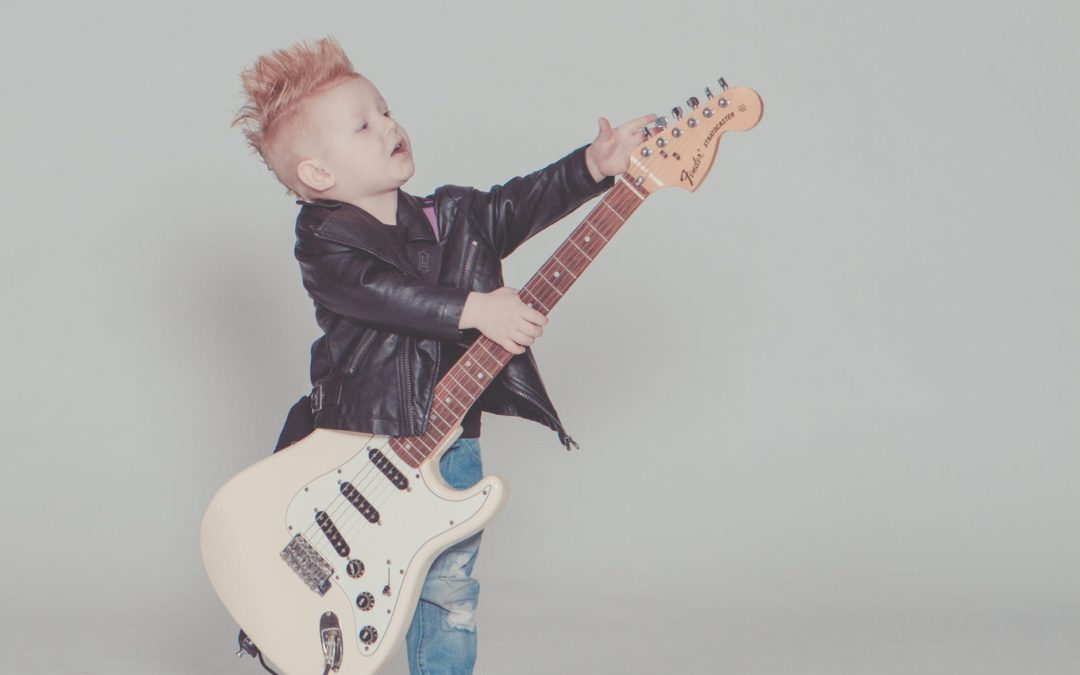 boy enjoys playing with his guitar