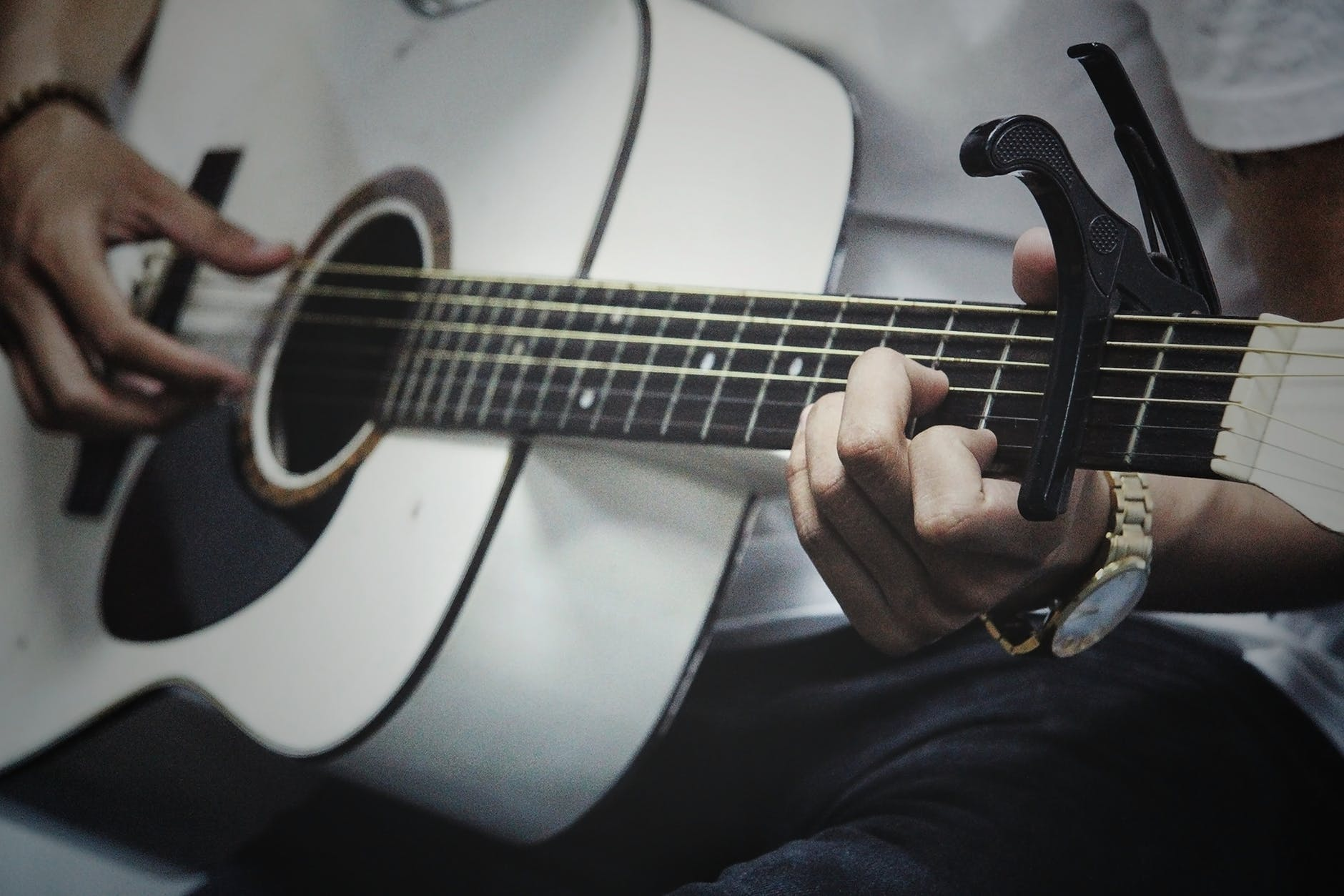 man playing a guitar using a capo
