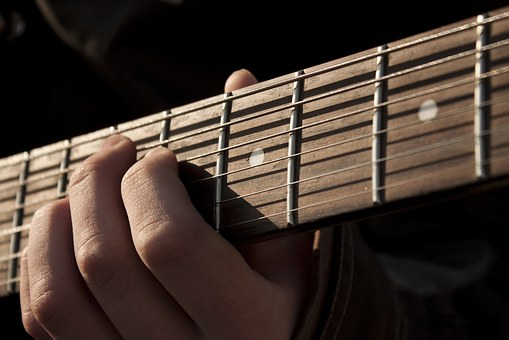 Hand playing guitar string