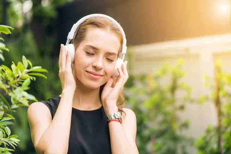 woman with white headphone and listening music