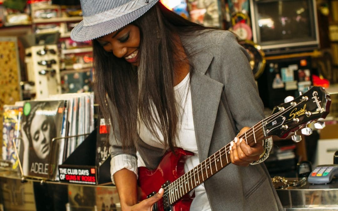 woman using a red guitar