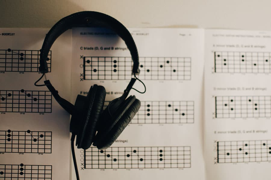 headphone on top a paper with guitar chords